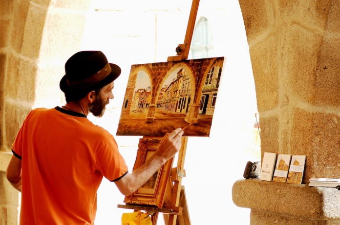 artist paints a picture on easel