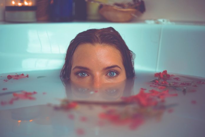 lady soaks in light blue bath tub of almond milk with red flowers floating
