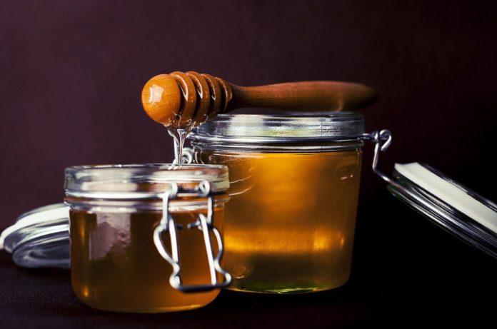 A honey dipper balanced on an open jar of honey.