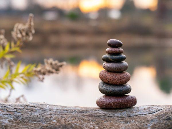 zen stones on fallen log with water reflected in background