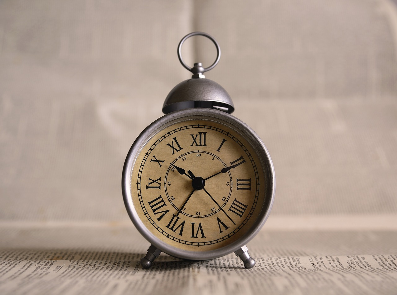 A silver alarm clock with a weathered face.