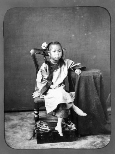 black and white photo of girl with bound feet
