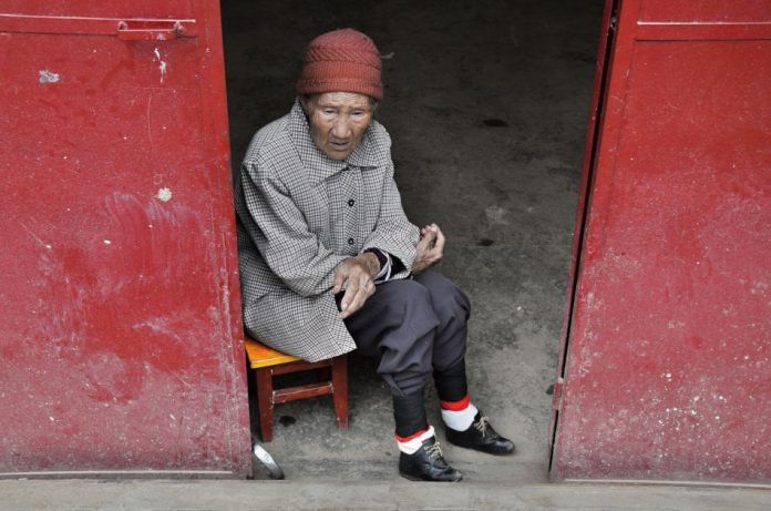An old chinese woman with bound feet in small shoes sitting in front of the house.