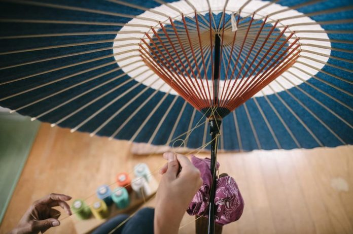 Japanese woman making a paper umbrella using traditional techniques.