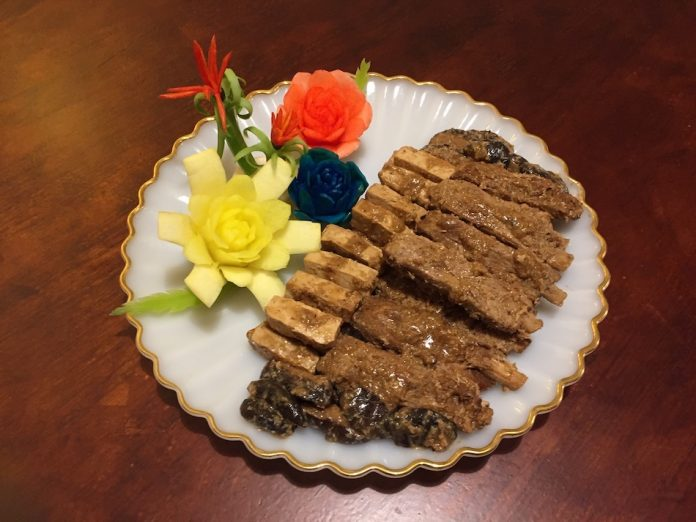 delicious stewed pork ribs with mushroom and tofu on a white plate with carrots and vegetables that are carved in the shape of flowers