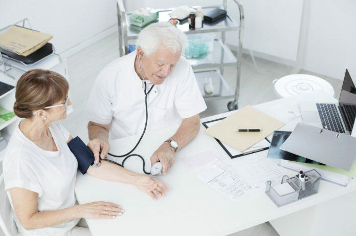 Man with white hair and white clothes takes the blood pressure of a woman with brown hair and white clothes as they sit together at a table containing a laptop, patient chart, and x-ray.