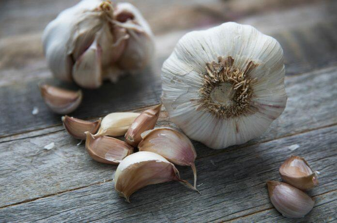 Cloves of garlic sitting on a wooden surface.