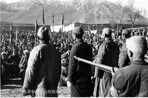 Group of Chinese peasants gathered together under the watchful eyes of several men holding guns during the Chinese Communist Party's 'Land Reform' movement.