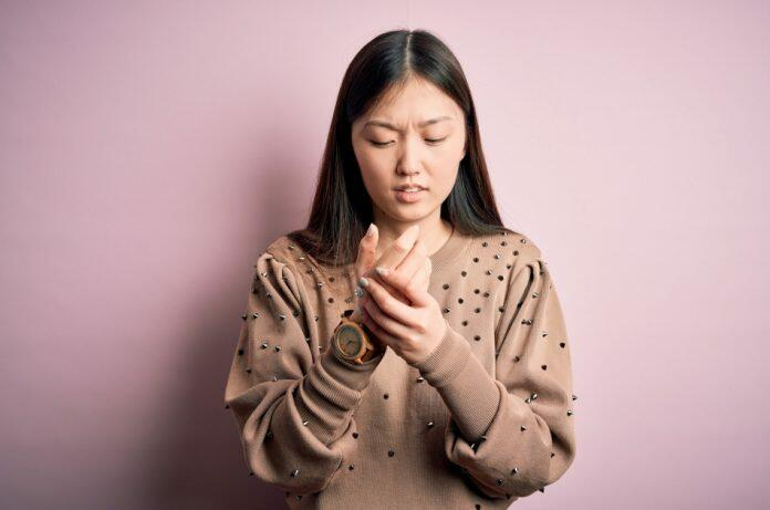 Young beautiful female Asian model wearing a fashionable and elegant sweater standing in front of a pink background rubbing her hand with a look of suffering on her face.