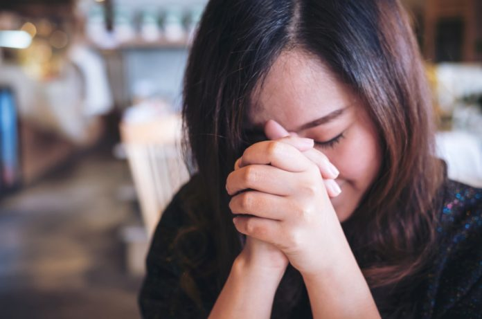 Asian woman with head bowed and hands clasped together praying.
