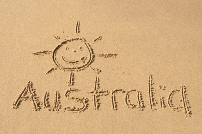 A picture of sun and the word Australia drawn in the sand.
