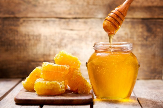 Honeycomb and jar of honey sitting on a wooden surface.