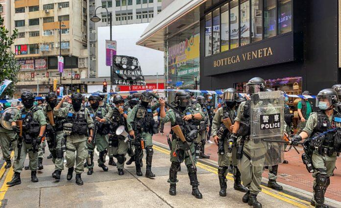 Hong Kong police in riot gear supressing people demonstrating for democracy and freedom.