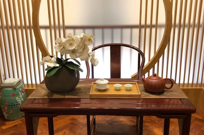 A small table with one chair set with a tea pot, tea cups, and a pot of white orchids.