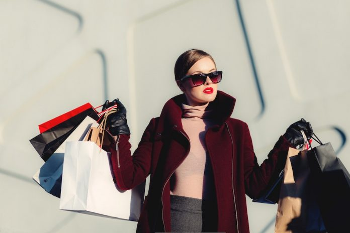 art of wanting less lady with sunglasses and lots of shopping bags