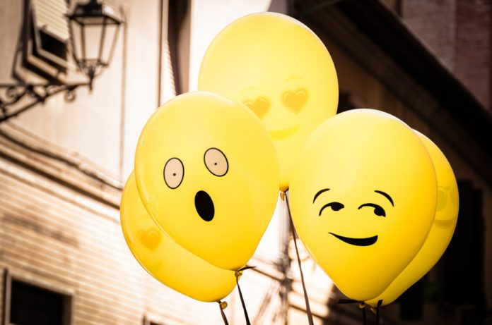 A group of yellow helium-filled balloons with funny emoji faces.
