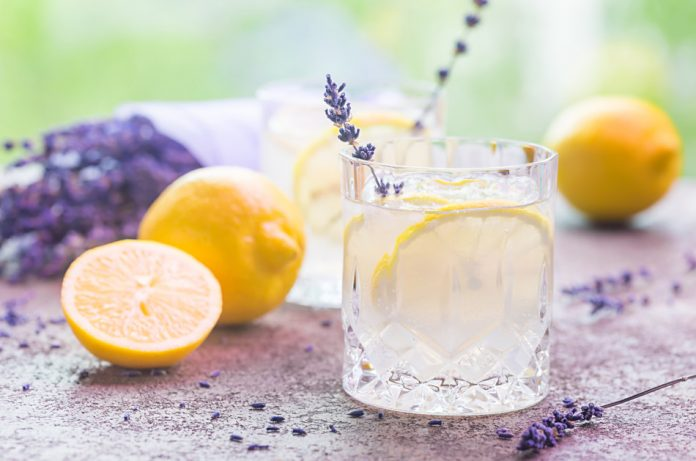 A glass of lemonade with lavender and lemons.