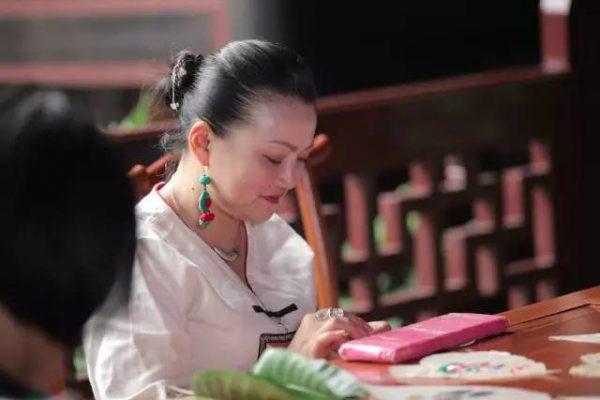 Yang Li, as she embroiders, wearing traditional Guizhou region Miao-style jewelry.