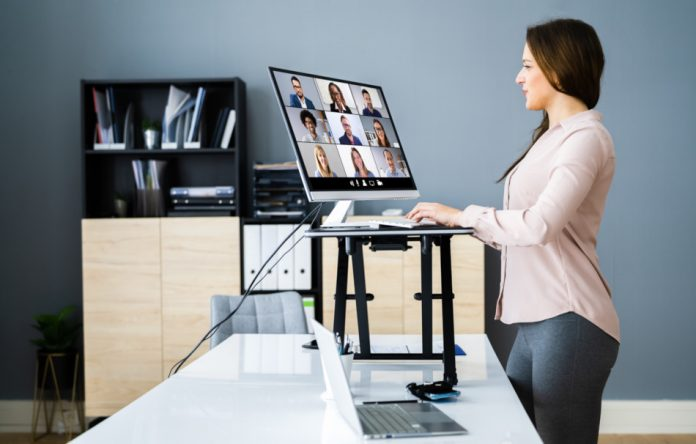 A woman stands as she works at an adjustable height desk.