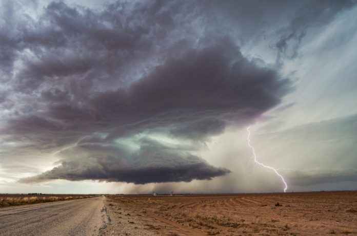 Dramatic dark clouds fill the sky ahead of a supercell thunderstorm with intense lightning.
