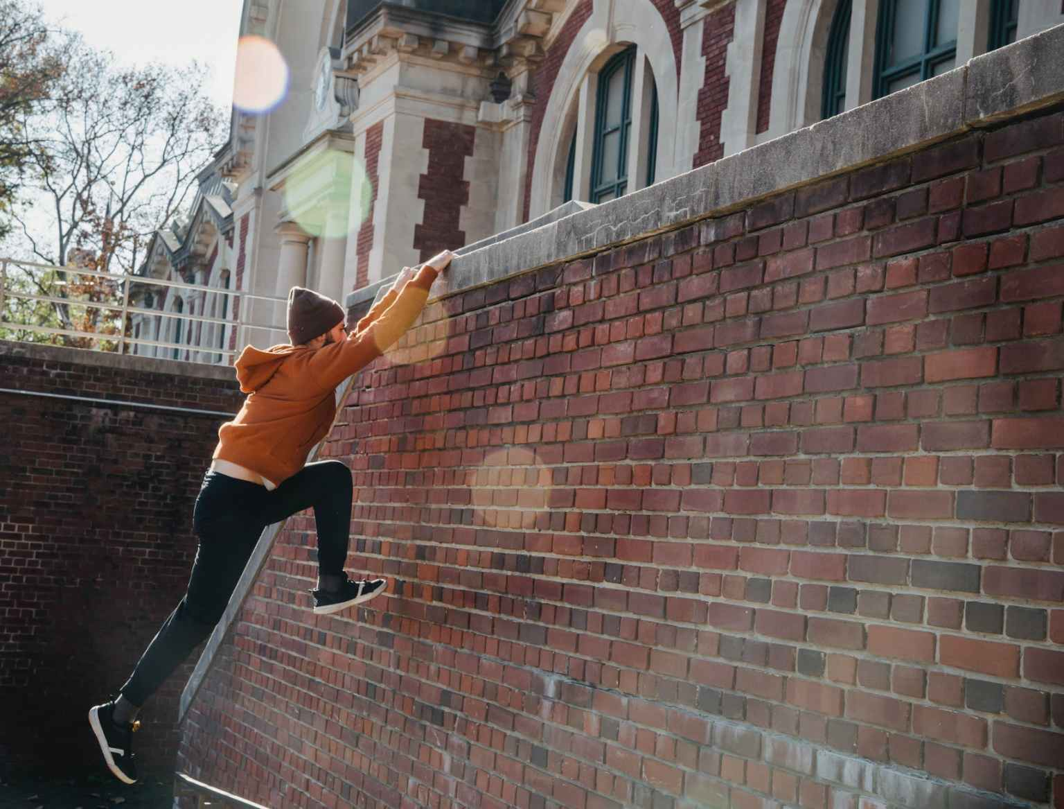 active man jumping on brick wall