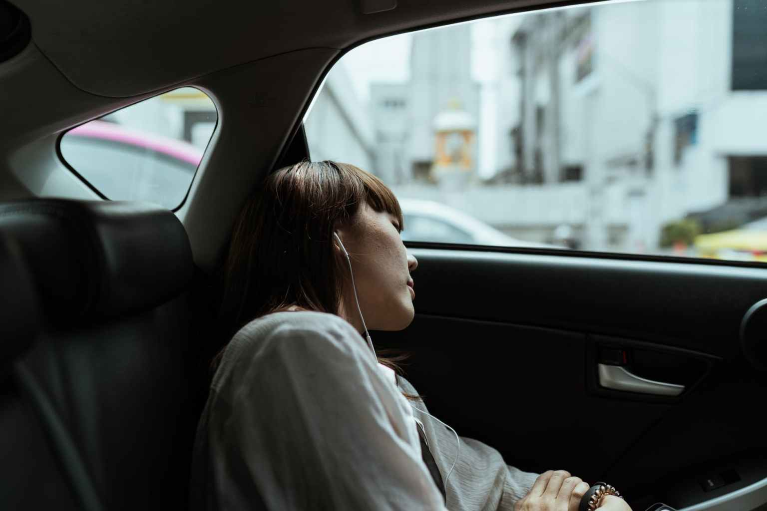 calm woman resting in car backseat with earphones