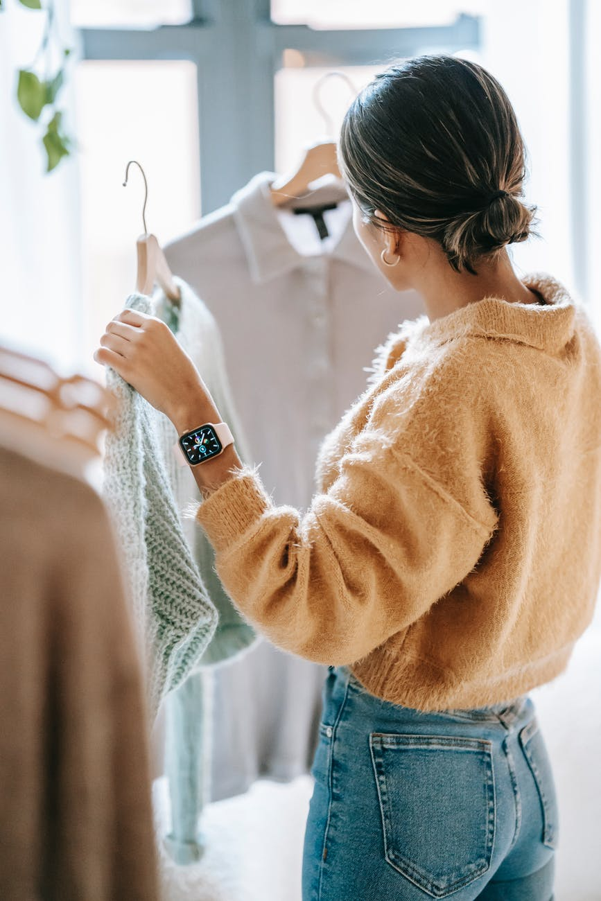 anonymous woman choosing outfit in store