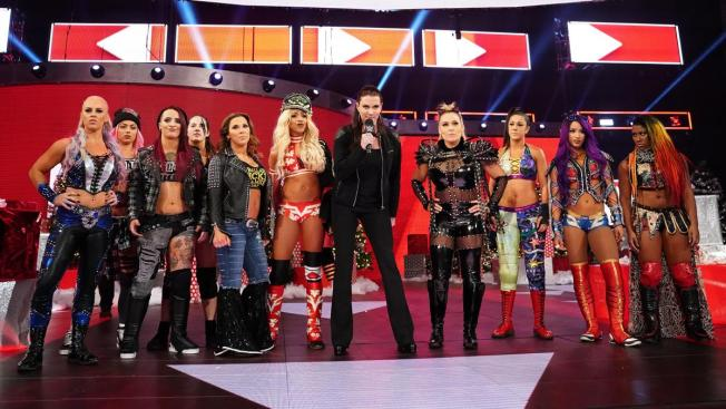 Stephanie McMahon flanked by the RAW women's division