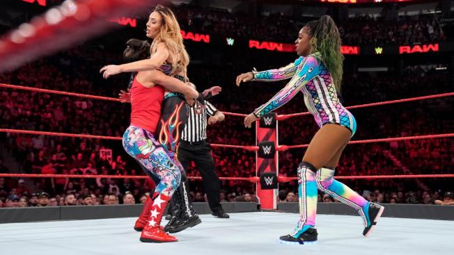 Bayley about to Bayley to Belly Peyton Royce, with Naomi looking on