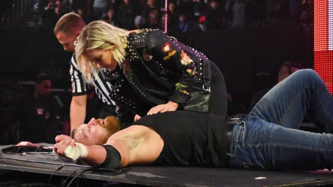 Renee Young kneels over Dean Ambrose