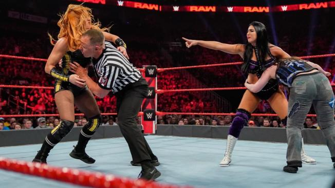 Becky Lynch tries to get at Billie Kay who is holding Nikki Cross