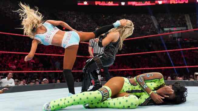 Carmella superkicks Natalya with Naomi laying i the foregroud