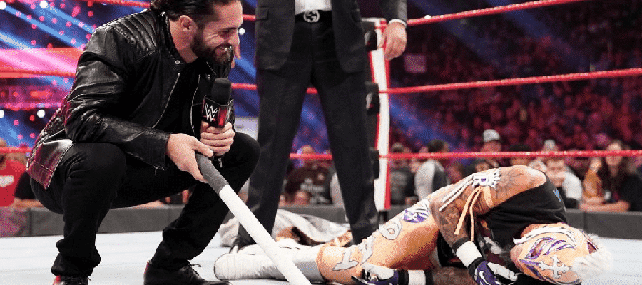 Seth Rollins crouched beside Rey Mysterio