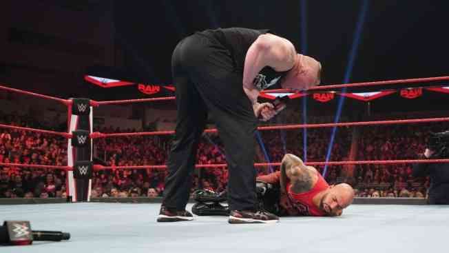 Brock Lesnar leans over Ricochet