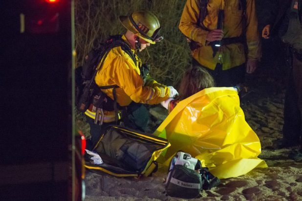 A Firefighter from Station 311 wraps a women's arm after she suffered burns from a warming fire in the Mojave River Bed. (Gabriel D. Espinoza, Victor Valley News)