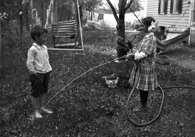 Children (6-7 years) playing with hose in garden