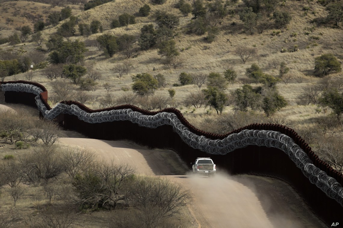 A Customs and Border Control agent patrols on the U.S. side of a razor-wire-covered border wall along the Mexico east of Nogales, Arizona, March 2, 2019.