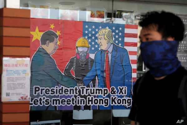 FILE - A pro-democracy protester walks past a poster featuring Chinese President Xi Jinping, left, and U.S. President Donald Trump at the campus of the University of Hong Kong, in Hong Kong, Nov. 6, 2019.