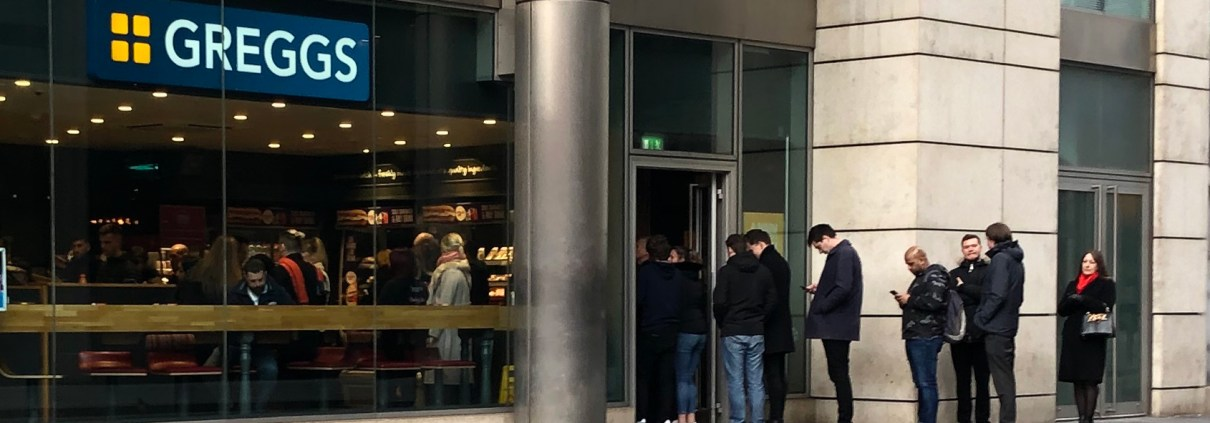 Lunchtime queue outside Greggs in Spinningfields, Manchester