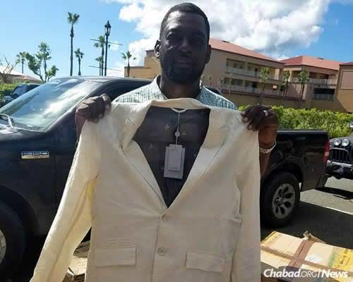 A man holds up a blazer he received on Sunday.
