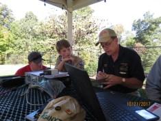 Wayne, N7QLK, explains ham radio to a Scout and his parent