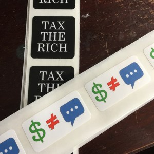 "Strips of bulk stickers including two designs. One, square with white text on black reads ""TAX THE RICH"" The second, rectangular, reads ""$ ≠ 💬"""