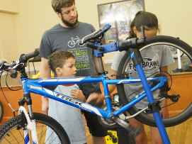Nic, Maisie, and Zack from Gearin' Up work on fixing a bike