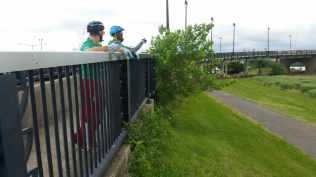 Two trail rangers look off into the distance chatting with each and standing on the rail of the South Capitol St bridge. They are both wearing gardening gloves from doing vegetation work on the trail.
