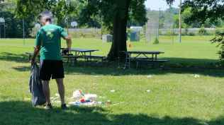A Trail Ranger faces away from the camera standing on the grass of Anacostia Park picking up trash. There is a big pile of trash next to his right foot. In the background is a big tree with picnic tables.