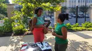 A woman Trail Ranger in the uniform green shirt faces away from the camera talking with a passerby wearing headphones, red pencil skirt and teal shirt. They are next to a table with lots of outreach materials.