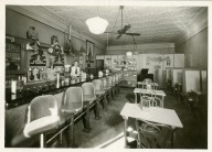 This is the earlier of two interior views of an Alma, Kansas soda shop. This view shows the lunch counter, booths and tables in the eatery.