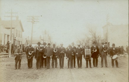 Members of the Alma Colored Band stand in the 200 block of Missouri Street at a celebration circa, 1900. Identified left to right are Ferdinand Herrmann, Sally Wallace, John Goodpasture, Bill Goodpasture, Freddie Owens, Tom Wallace, Pickwith McDonald, Sam Bennett Jim Cruters, Roy Wallace, Jessie Davis, Bill Cruters, John Holford, and Buddy Gardenhire.