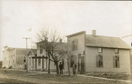 Ferdinand Herrmnn, right, and his son, Fred, stand in front of their shoe shop West Main Street in Alma, Kansas. Notice the boot hanging on the building by the door. To the west of the shoe shop one can see Herrmann's Harness Shop, August Falk's Alma Marble Works, a tailor shop, and Falk's Opera House.