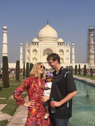 Toddler hugged happily by parents as they travel; photo in front of Taj Mahal